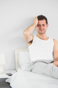 Man with headache sitting in bed: CannaLinq CBD Oil Blog